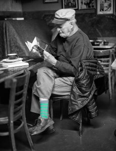 Photo of Lawrence Ferlinghetti reading a book.