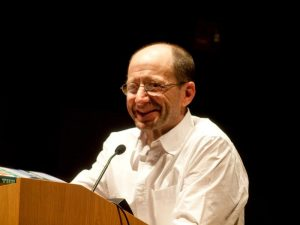Photo of Rick Bass smiling, standing at a lectern.