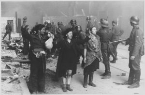 Photo of Jews with their armes raised surrounded by German troops in the Warsaw ghetto.