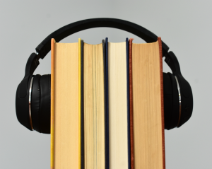 Photo of headphones over a stack of books.