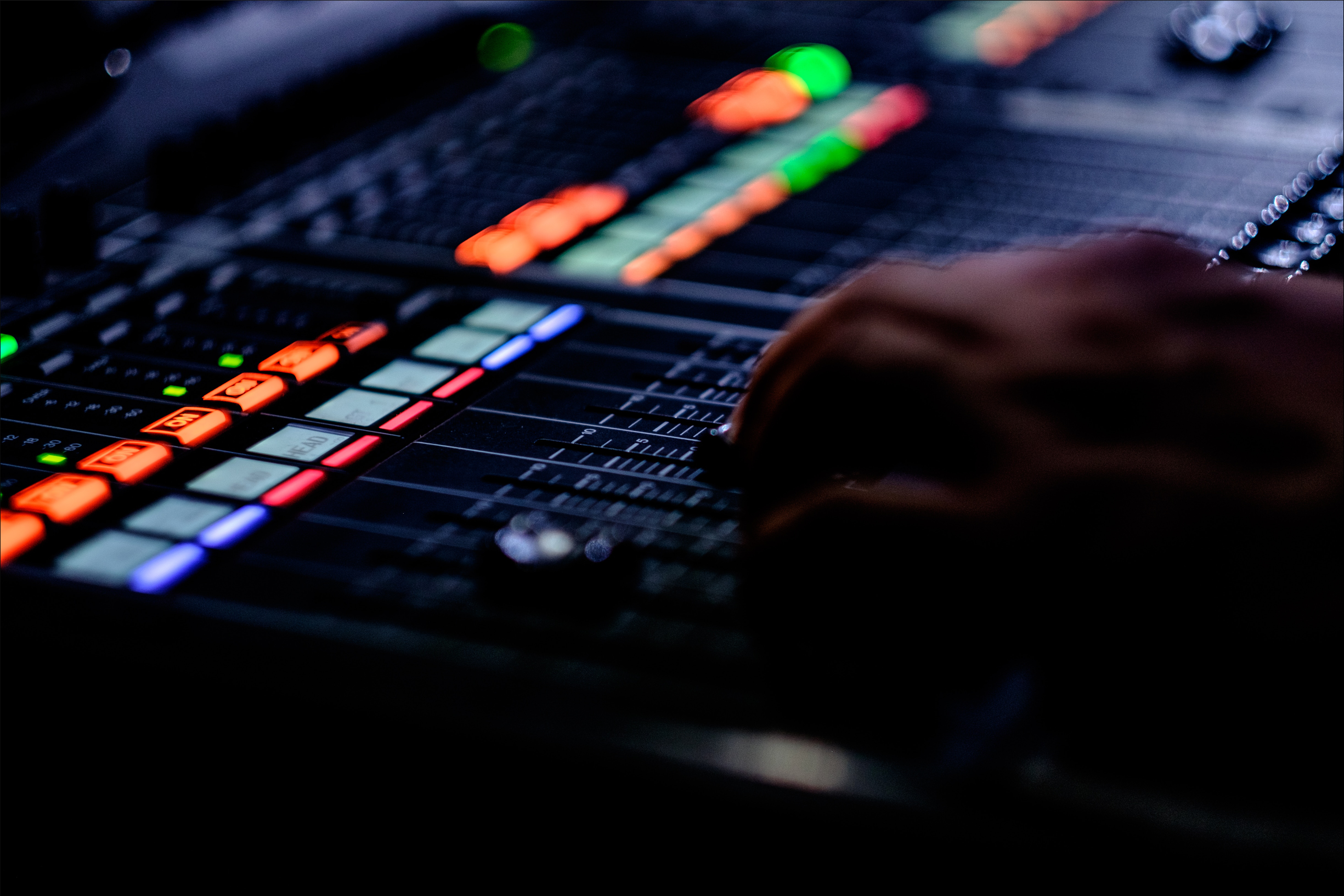 Photo of a hand using a sound mixing table.