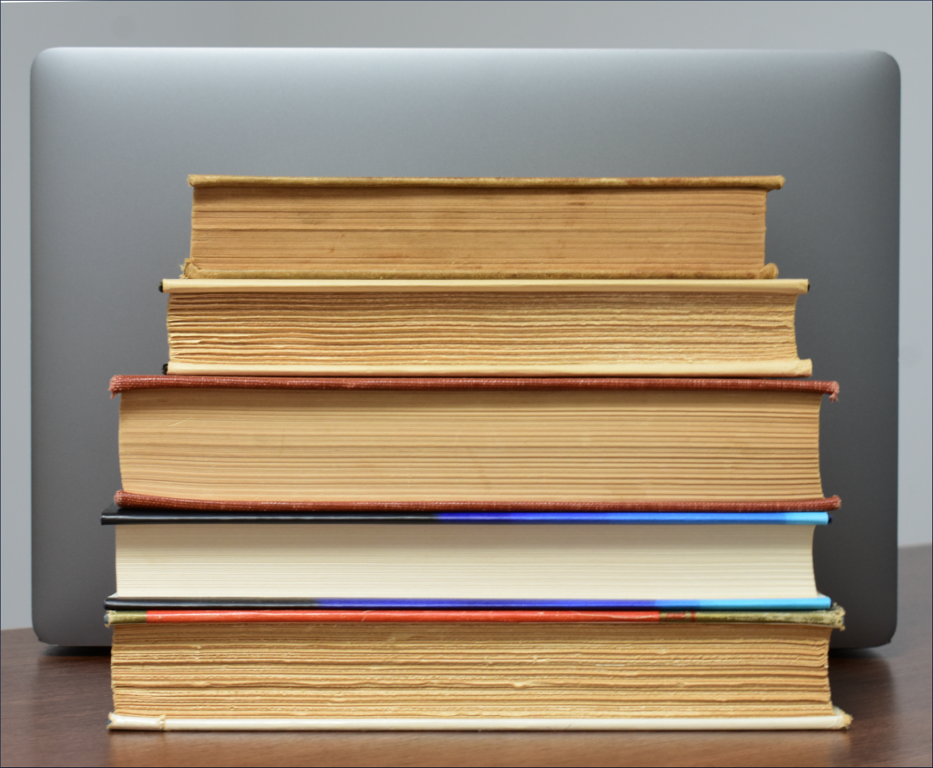 A stack of books in front of a laptop computer.