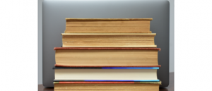 Books stacked in front of a laptop computer.