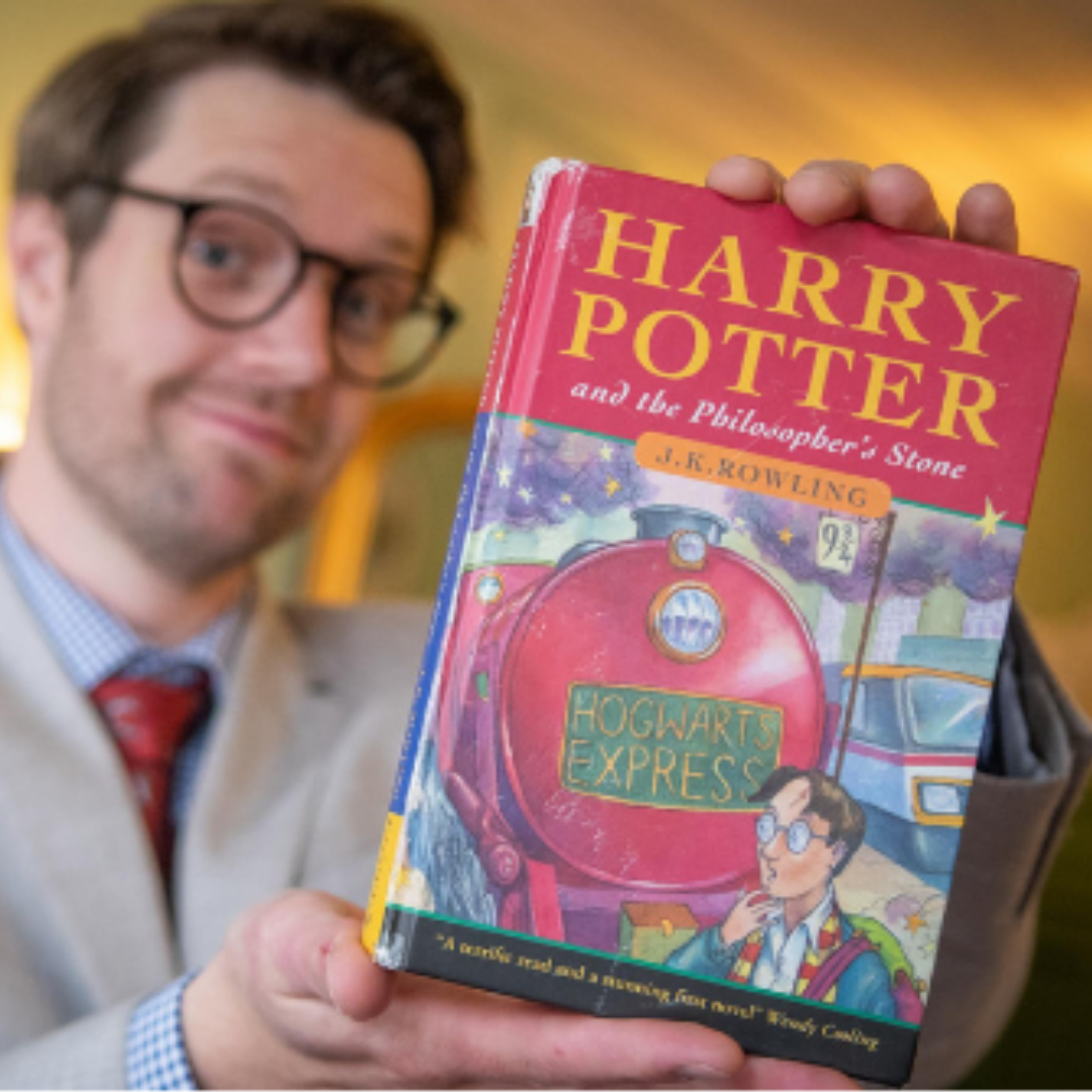 Man holding a first edition Harry Potter book.