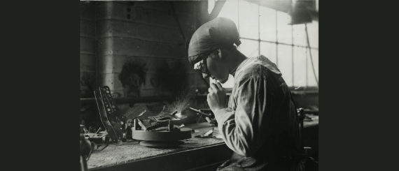 Woman in black and white wearing goggles using tools on a workbench.
